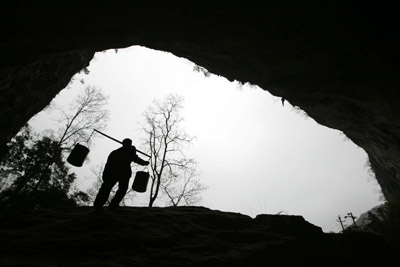 An ethnic Miao man carrying buckets walks out of a huge cave at a remote Miao village in Ziyun county