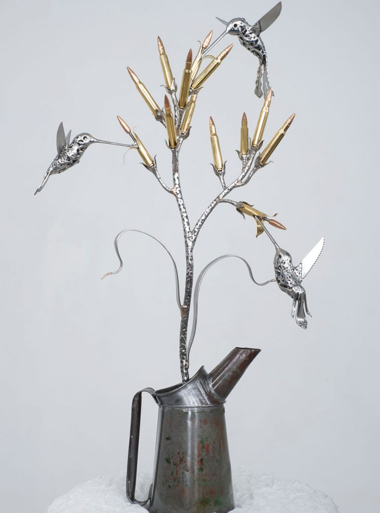 The base is a vintage oil can filled with barbed wire and resin. The birds are made from old spoons, knives, nuts and bolts, The flowers are inert 7.62 full metal jacket bullets, and the stalk is scrap stainless steel covered in weld.