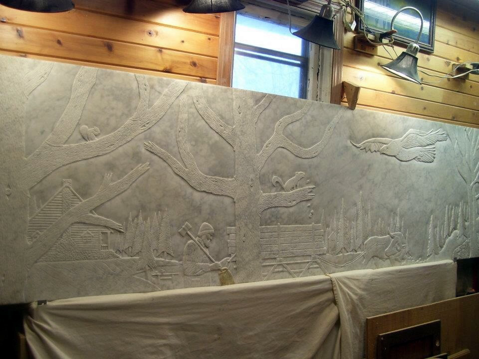 Paul Bunyan scene hand carved from an old marble bar top.