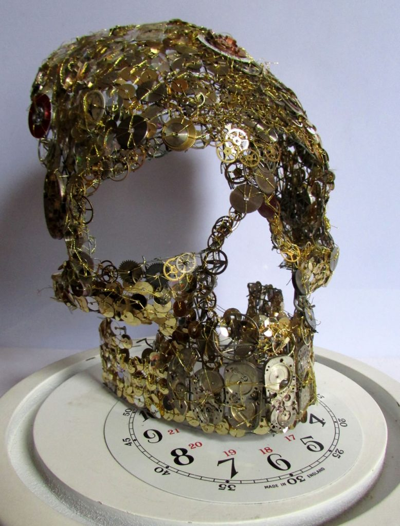 Skull is made from a wire frame shaped by hand, then hand stitched with gold color thread, various watch parts, watch faces, cogs, hands, and gears over the skull mixed with old sequins.