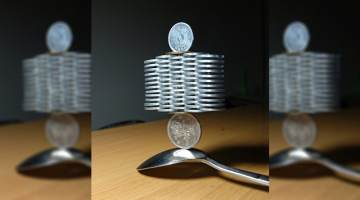 coin stacking tower balanced on spoon