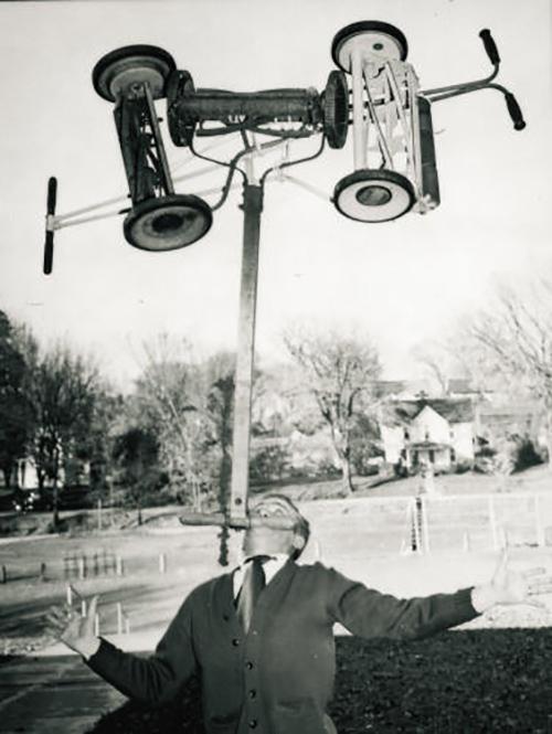 man balancing lawn mowers