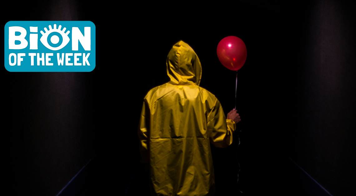 person in yellow raincoat with red balloon