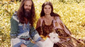 Single horned goat with new age man and woman
