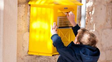 Child putting a letter in a mailbox